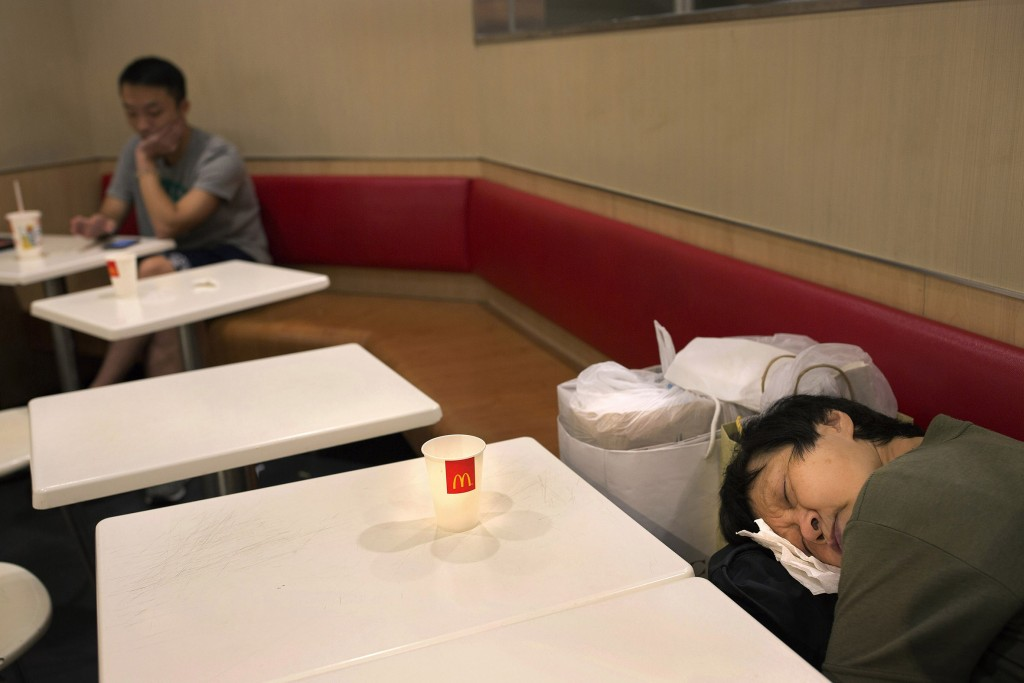 "In this Oct. 30, 2015 photo, a woman sleeps with her belongings at night in a 24-hour McDonald's branch in Hong Kong. The recent death of a woman at a Hong Kong McDonald's, where her body lay slumped at a table for hours unnoticed by other diners, has focused attention on the city's ""McRefugees"" down and out people who spend their nights the fast food outlet's 24-hour branches because they've nowhere anywhere else to go. (AP Photo/Vincent Yu)"